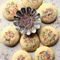 Vanilla Bean Shortbread Cookies are round, light colored cookies with multi-colored sugar on top.
