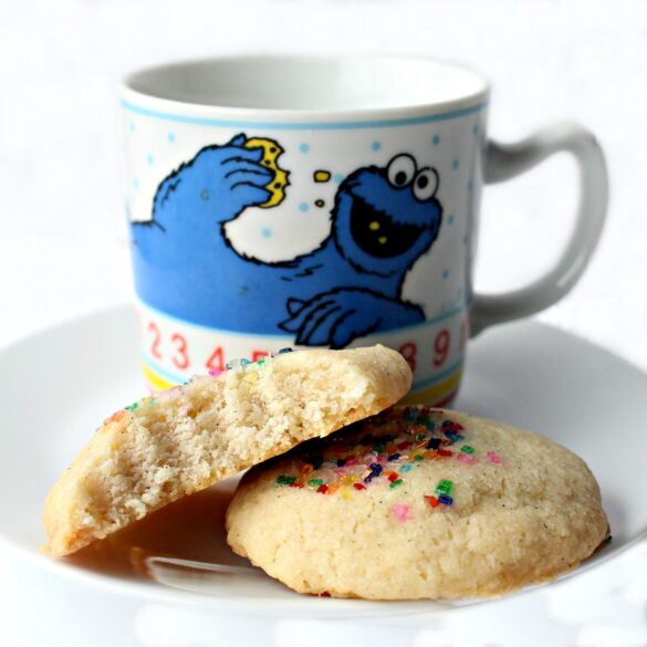 Two Vanilla Bean Shortbread Cookies, one with a bite showing the crunchy interior, on a plate with a Cookie Monster mug.