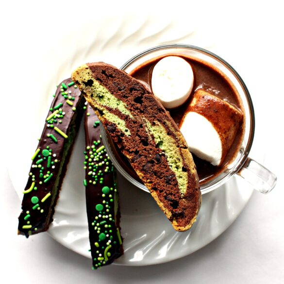 Chocolate Mint Biscotti on a plate with a mug of hot chocolate with marshmallows.