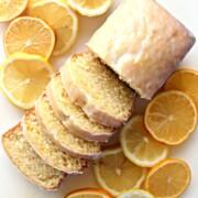 Iced Lemon Loaf sliced to show soft, dense interior crumb displayed with sliced lemons