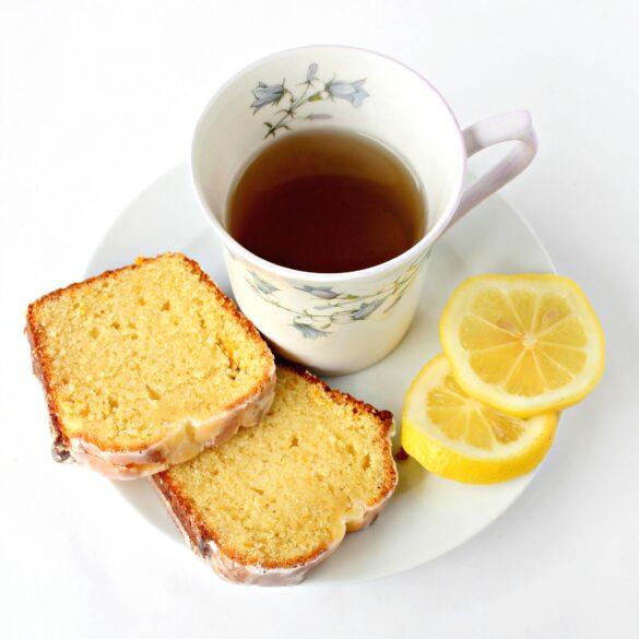 Lemon Loaf slices with a mug of tea and lemon slices