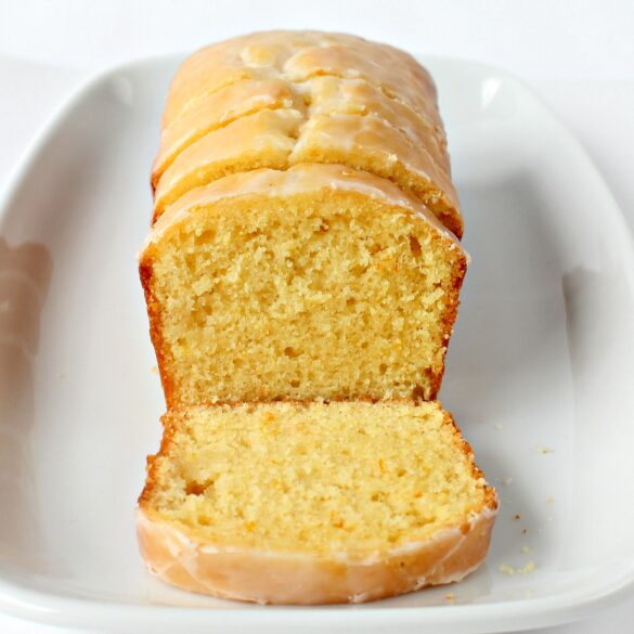 Close up of loaf with lemon yellow slice of cake topped with light yellow lemon glaze