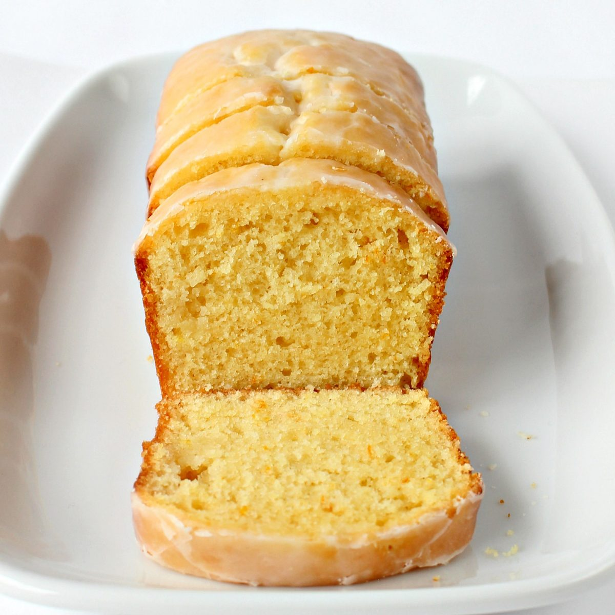 Close up of loaf with lemon yellow slice of cake topped with light yellow lemon glaze .