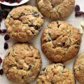 Cranberry White Chocolate Cookies, large and golden brown, on a board with chopped white chocolate and a bowl of cranberries