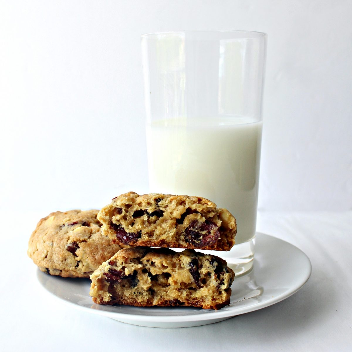 Cookies on a white plate with a glass of milk.