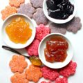 Butter cookies cut out in flower shapes, each dipped in orange, pink, or purple sparkling sugar, scattered on a white background with 3 little white bowls holding strawberry, peach, or blackberry jam.