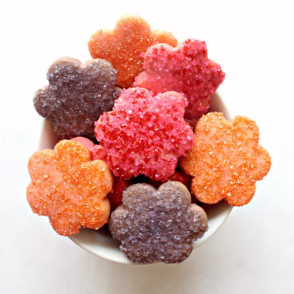 Looking down onto the top of a bowl filled with orange, pink, and purple cookies cut out in daisy shapes.
