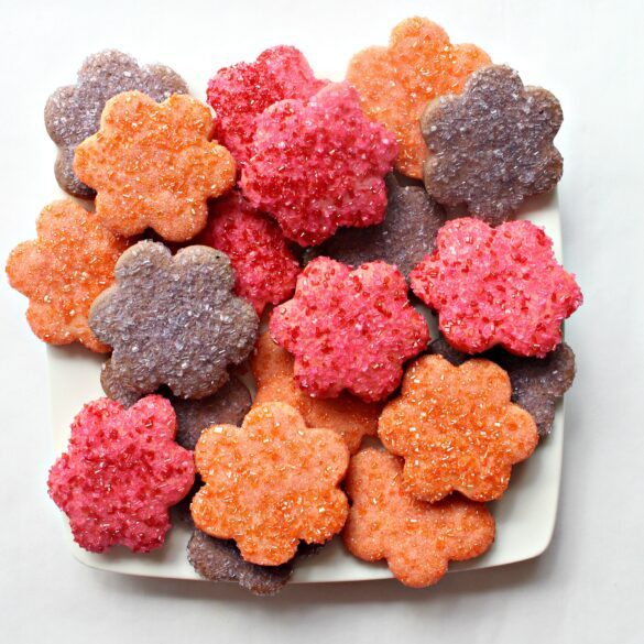 Flower shaped cookies covered in pink, orange, or purple sparkling sugar on a square white serving platter.