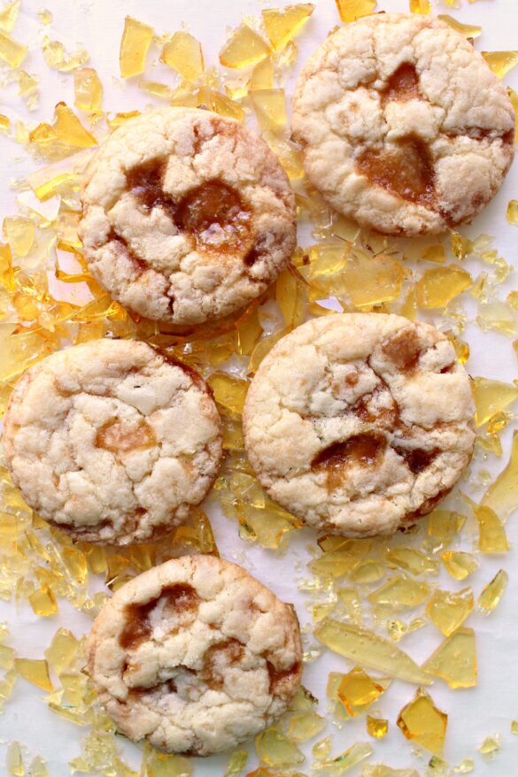 Butter cookies, with pools of melted caramel on top, lying on shards of caramel candy.
