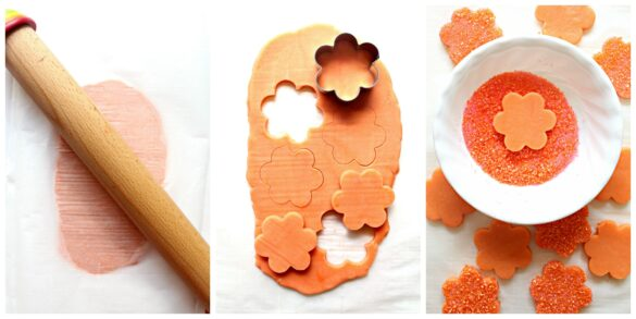 Collage of 3 photos. Photo #1 shows dough rolled out between 2 sheets of parchment with a wooden rolling pin on top. Photo #2 shows the rolled out orange dough with flour shaped cookies being cut out with a cookie cutter. Photo #3 shows and orange flower shaped cutou cookie being dipped in a white bowl filled with orange decorating sugar.