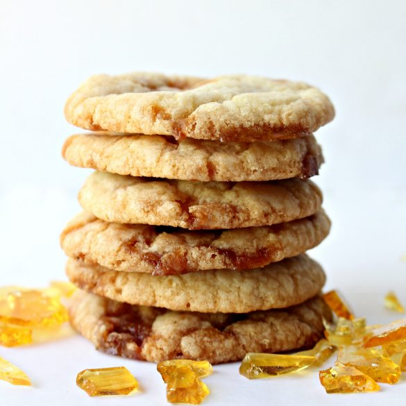 Stack of cookies showing thin crispy edges with hardened caramel candy showing through.