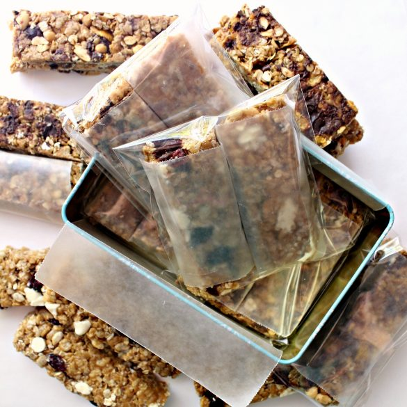 Granola bars being packed for shipping in a rectangle cookie tin are wrapped in wax paper before being put in cellophane bags.