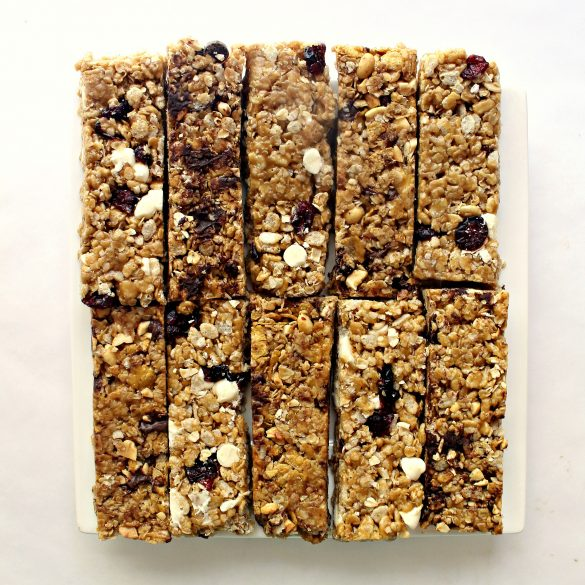 10 granola bars lined up on a square white serving plate