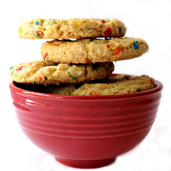 Side view of stack of cookies in a red bowl showing the thick, rounded edges of the cookies.