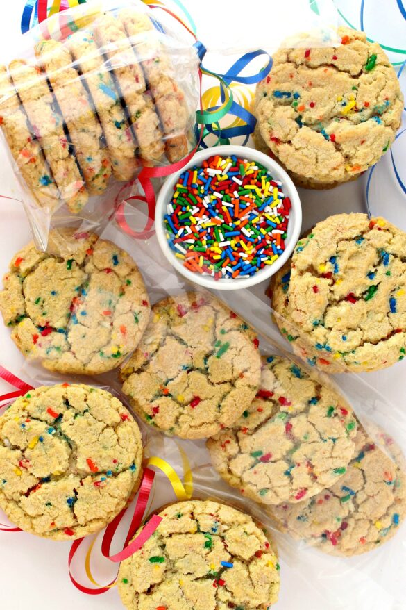 Funfetti Sugar Cookies, with rainbow sprinkles, a bowl of sprinkles and cookies wrapped in  clear cellophane bags.