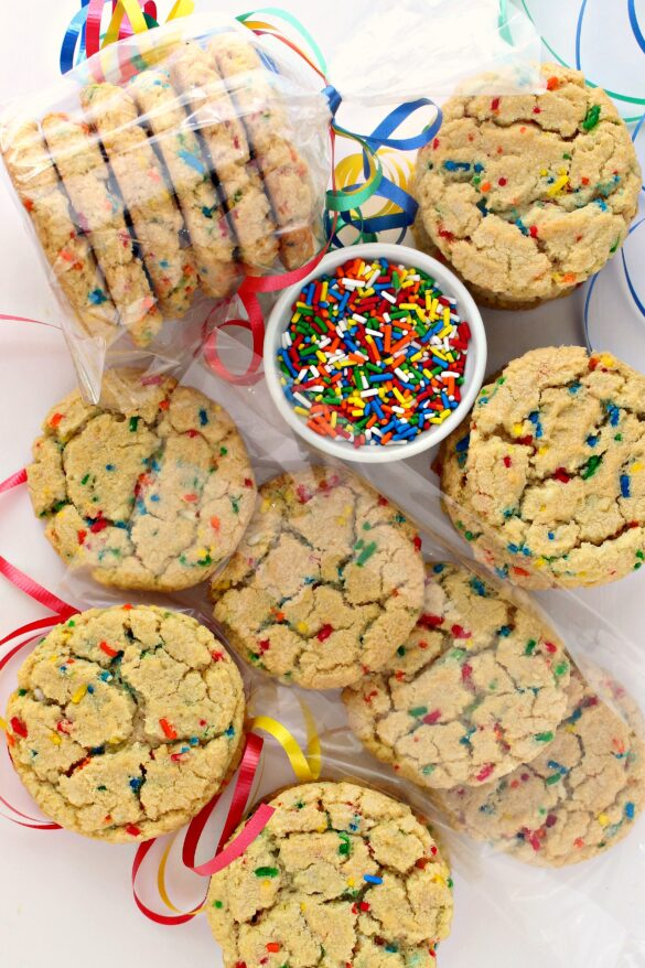 Funfetti Sugar Cookies, with cracked tops and speckled with rainbow colors from the sprinkles inside, on a white background with a bowl of sprinkles, ribbon, and 6 cookies wrapped in a clear cellophane bag.
