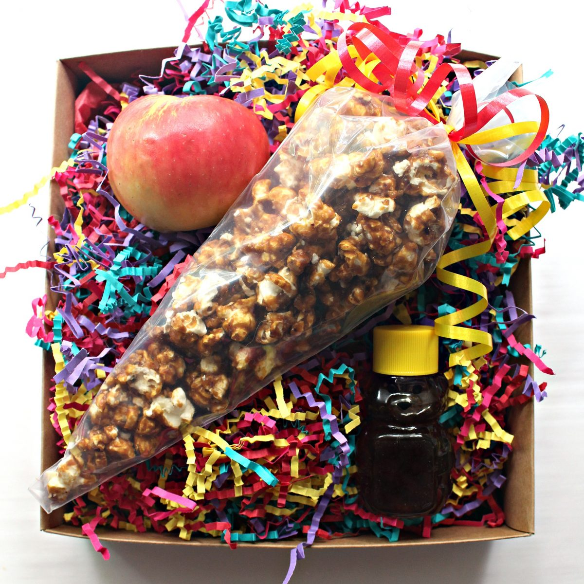 Gift package with rainbow raffia, apple, honey bear, and a clear cone bag filled with popcorn.