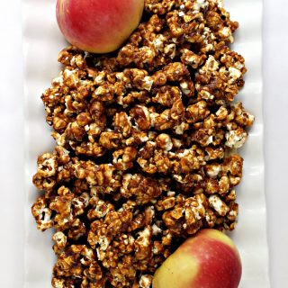 A white serving tray filled with Apples and Honey Caramel Popcorn and two apples