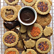Homemade Graham Crackers Sandwich Cookies with pumpkin cutouts, filled with melted chocolate and sprinkles