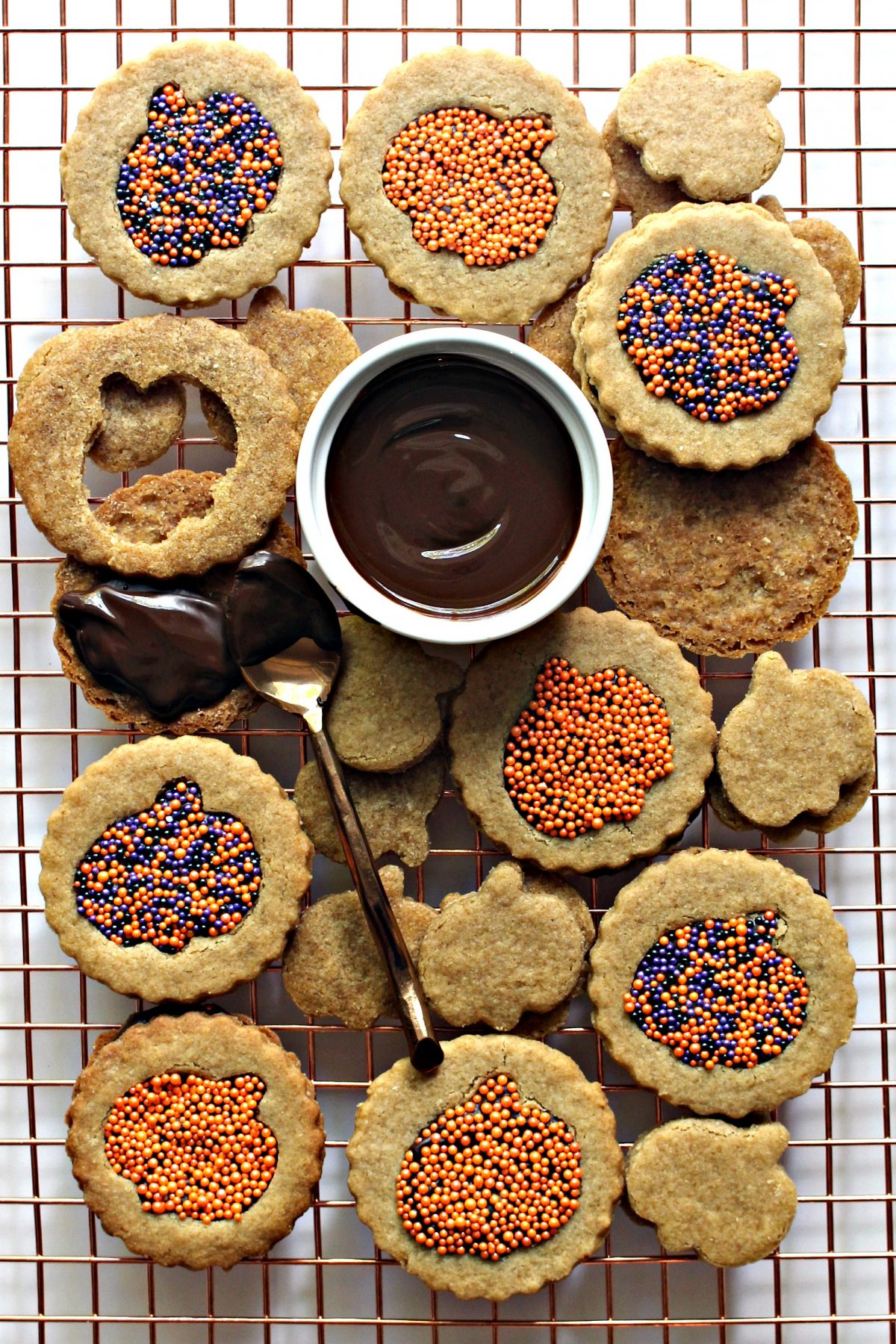 Homemade Graham Crackers Sandwich Cookies with pumpkin cutouts, filled with melted chocolate and sprinkles.