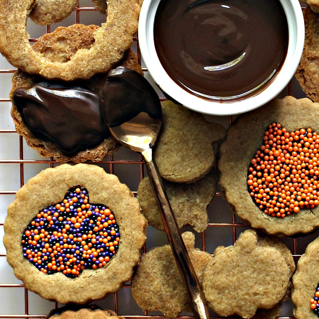 Close up of graham cookies sandwiched with melted chocolate peeking through a pumpkin cutout with sprinkles.
