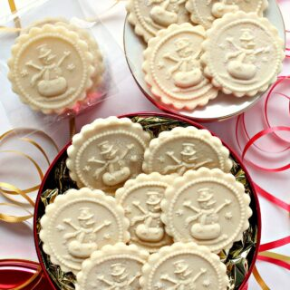 Flat discs of marzipan imprinted with a snowman cookie stamp.