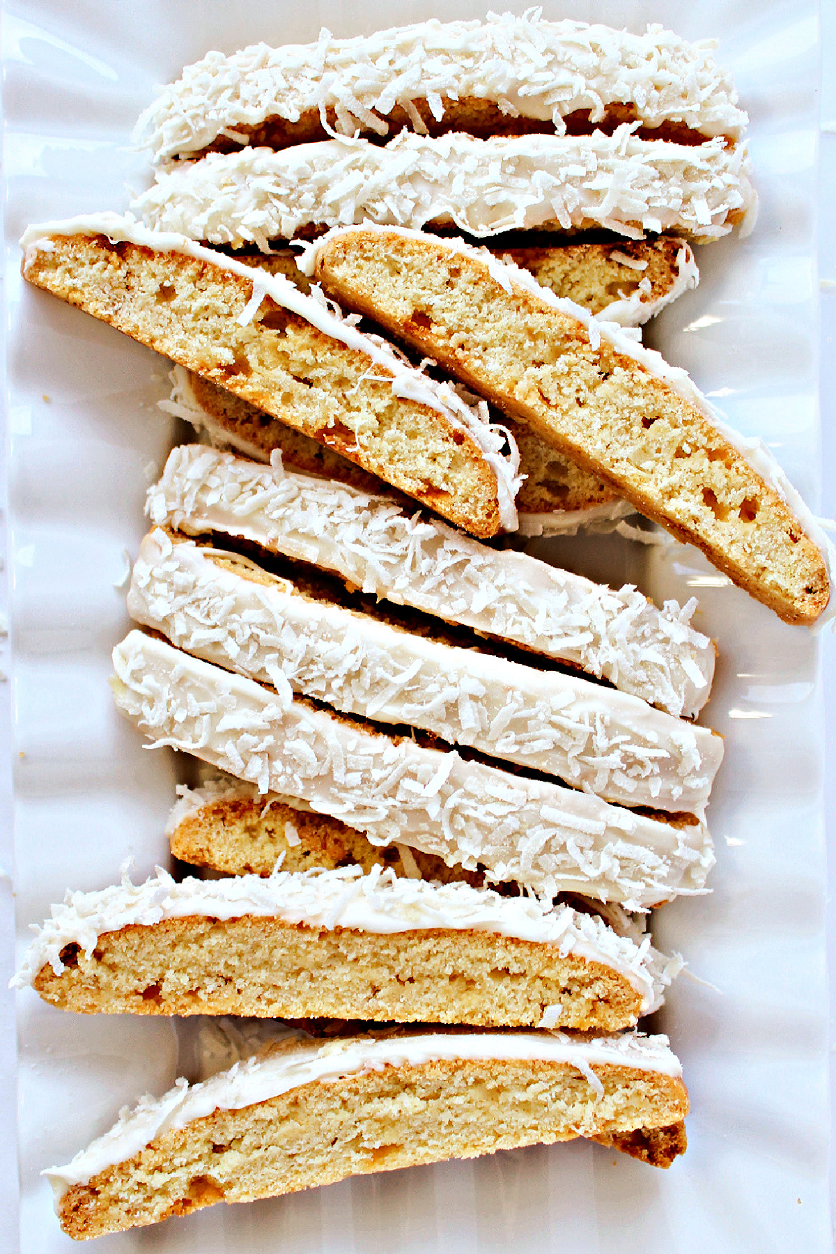 Sliced Coconut Biscotti topped with white chocolate and shredded coconut on a white platter.