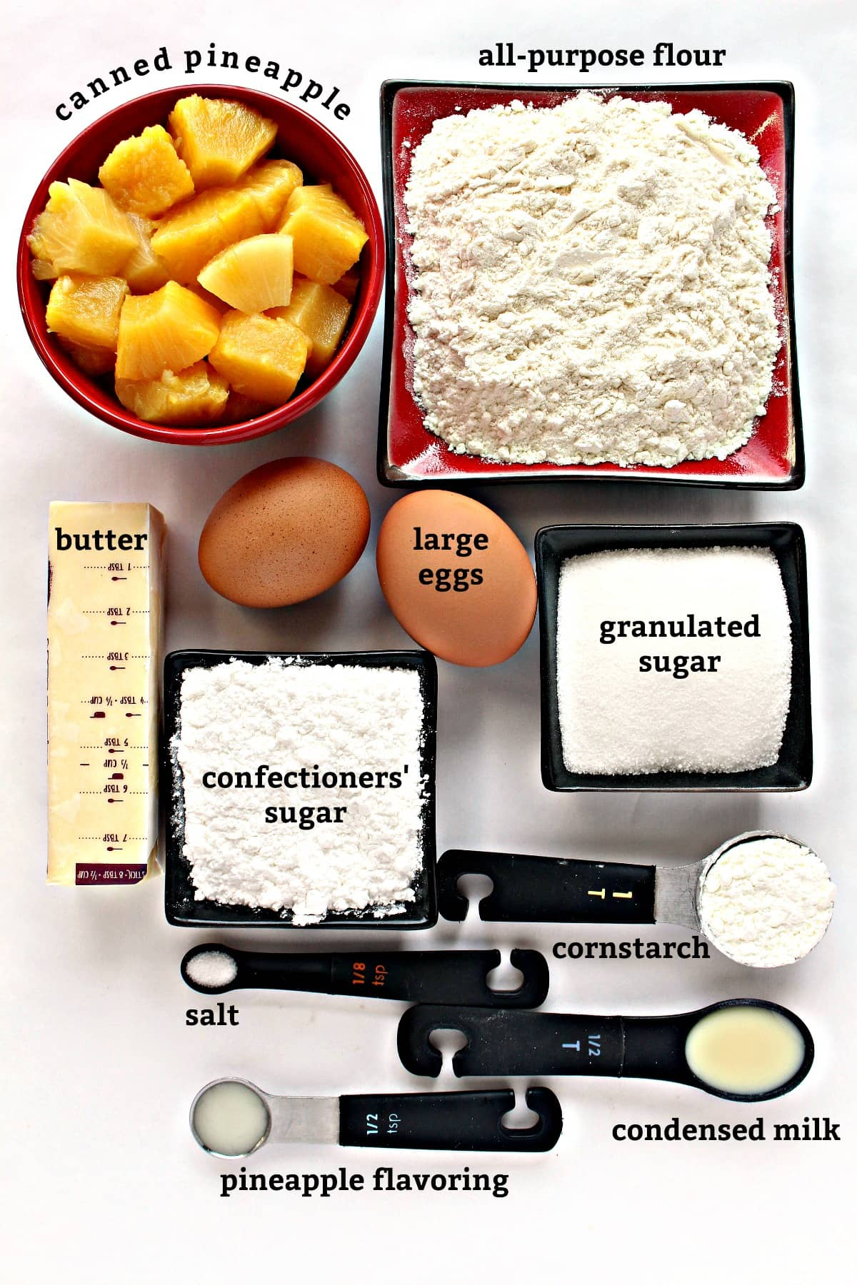 Recipe ingredients with text labels: canned pineapple, flour, butter, eggs, sugar, cornstarch, condensed milk, pineapple flavoring.