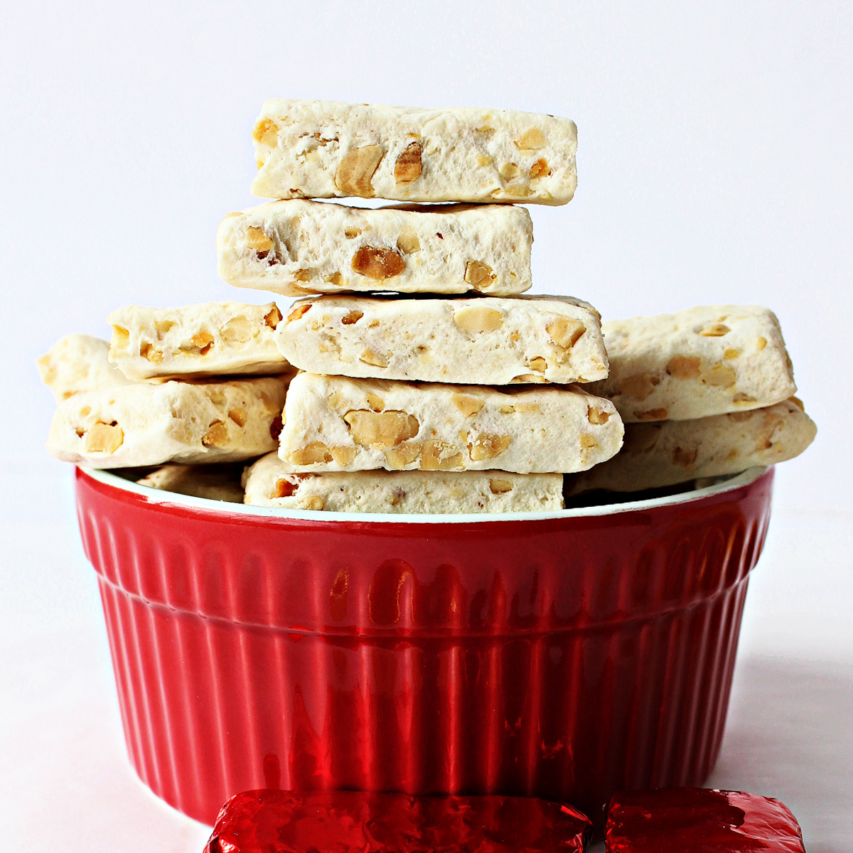 Photo taken from side showing cut edges of stack of milk candy nougat in red bowl.
