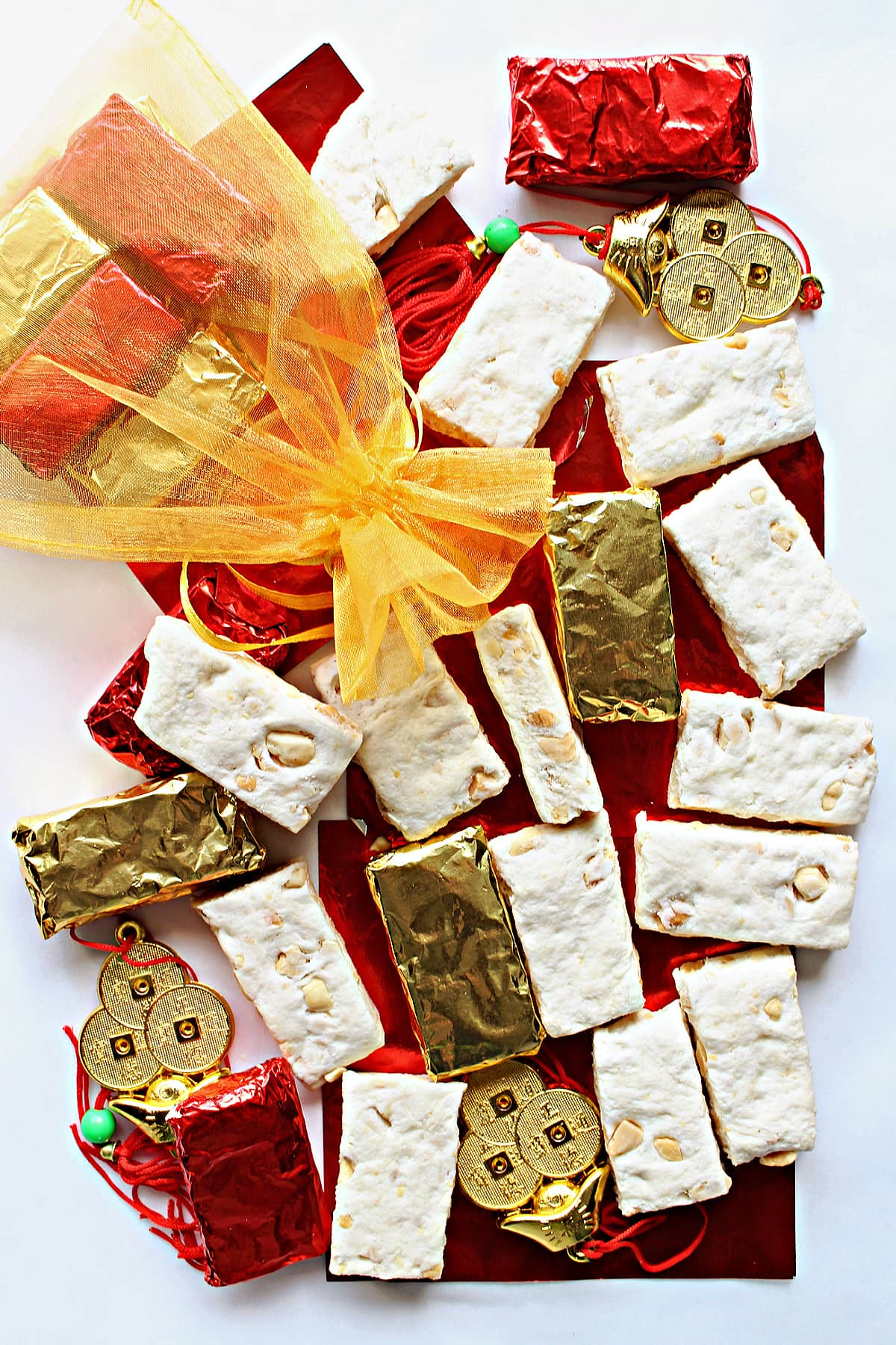 White rectangles of nougat peanut candy with some wrapped in gold and red foil.