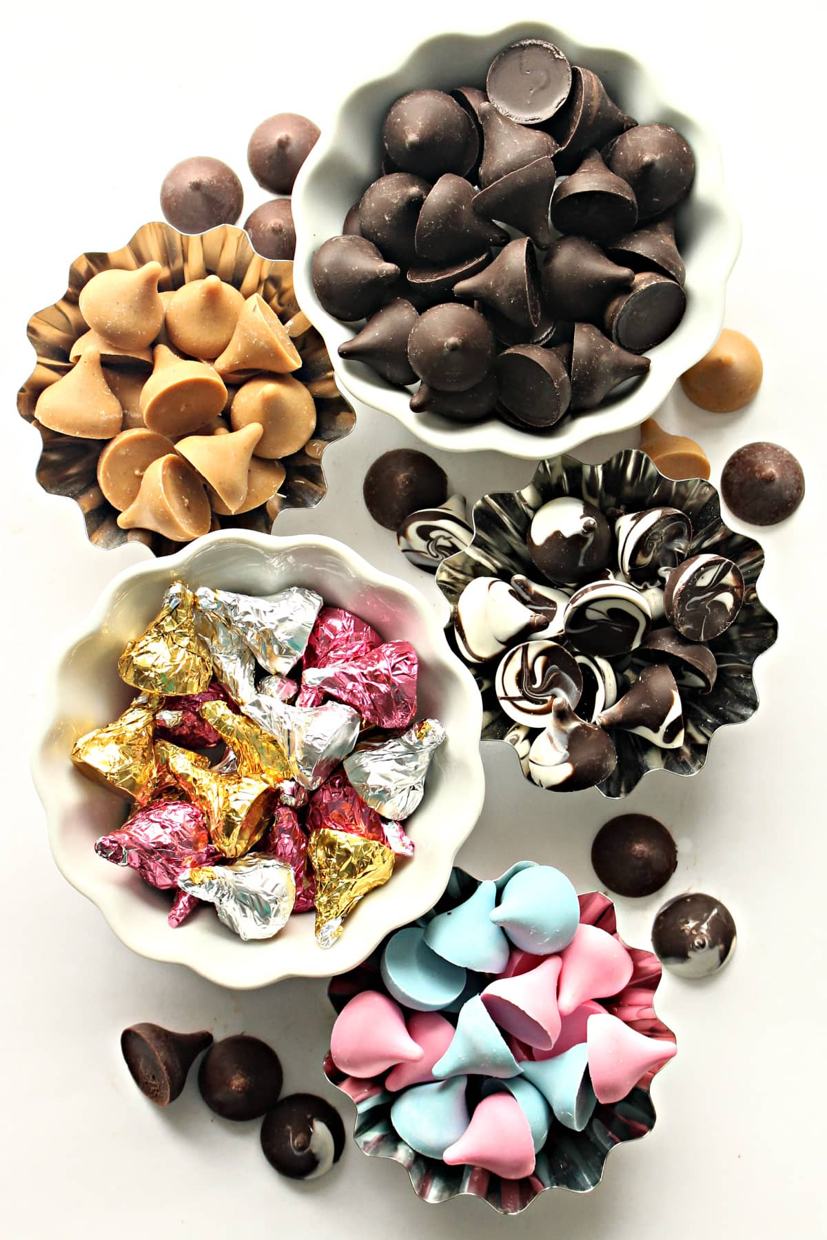 Bowls of Chocolate Kisses with different colors and flavors: chocolate, butterscotch, swirls, foil wrapped, pink, blue.