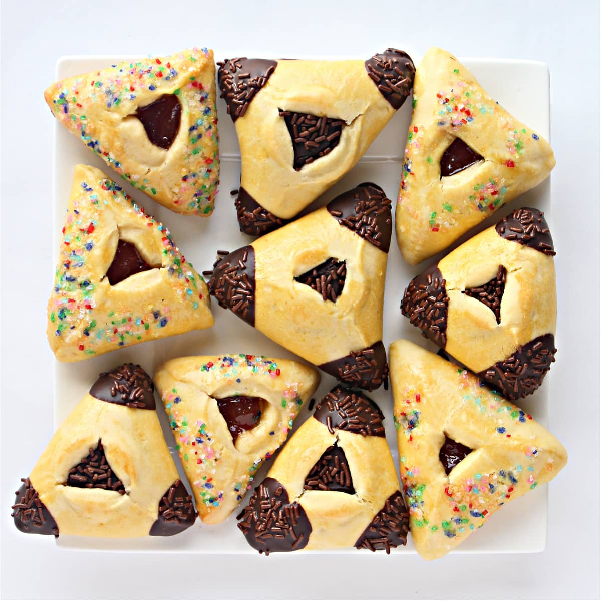 Triangle pocket cookies decorated with chocolate or colored sugar on a square platter.