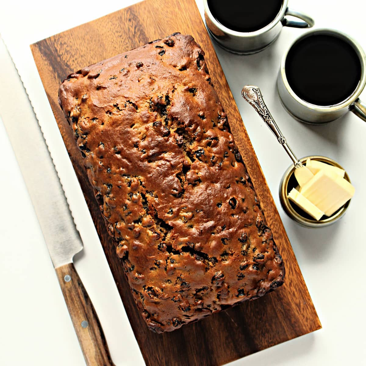Brown loaf of Tea Brack on wooden cutting board next to knife, butter, and coffee mugs.