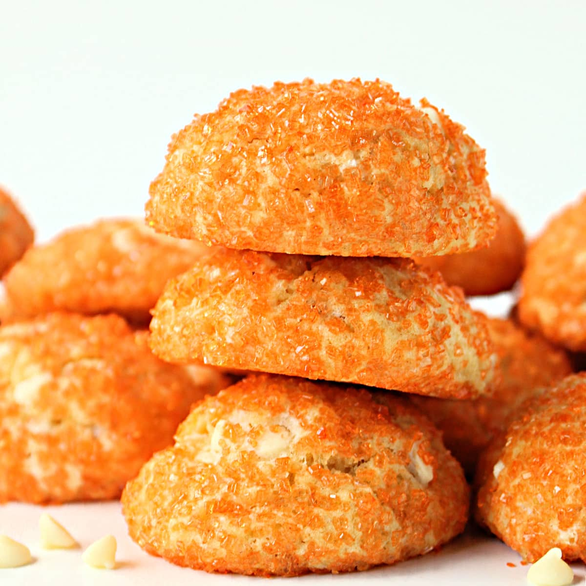 Stack of puffy cookies coated in orange sparkle sugar.