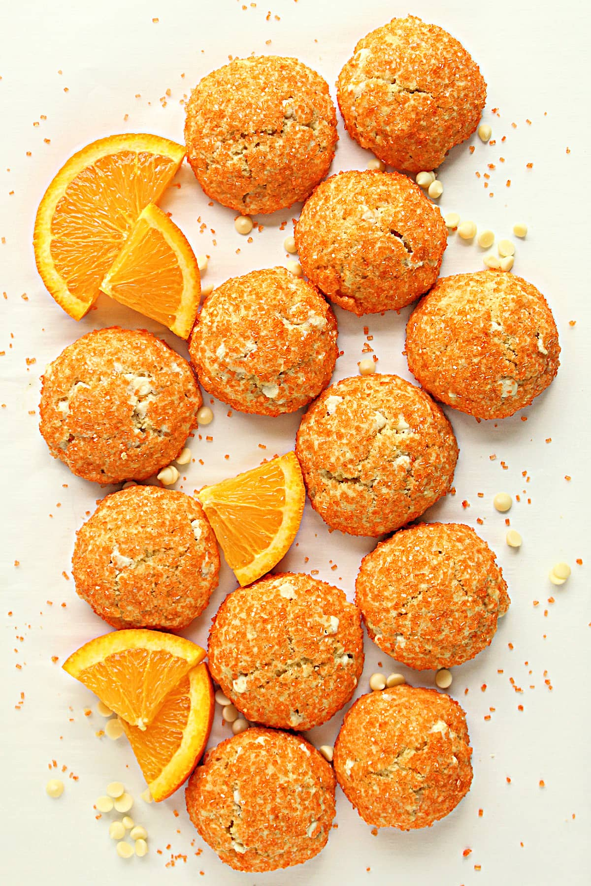 Cookies covered in orange sugar on a white background with orange slices, sugar, and white  chips.