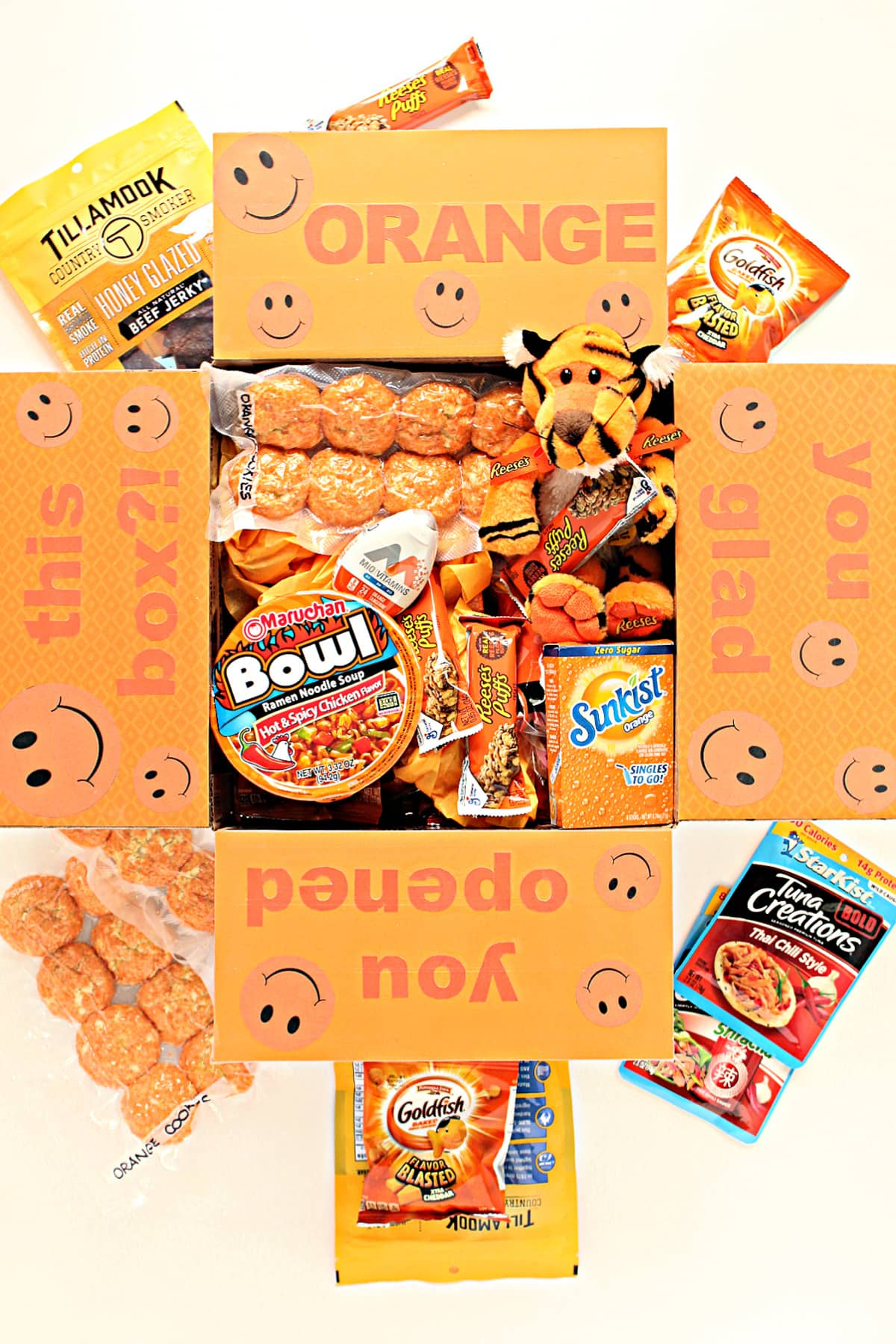 Care package box filled with orange packaged treats and orange box decorated box flaps.
