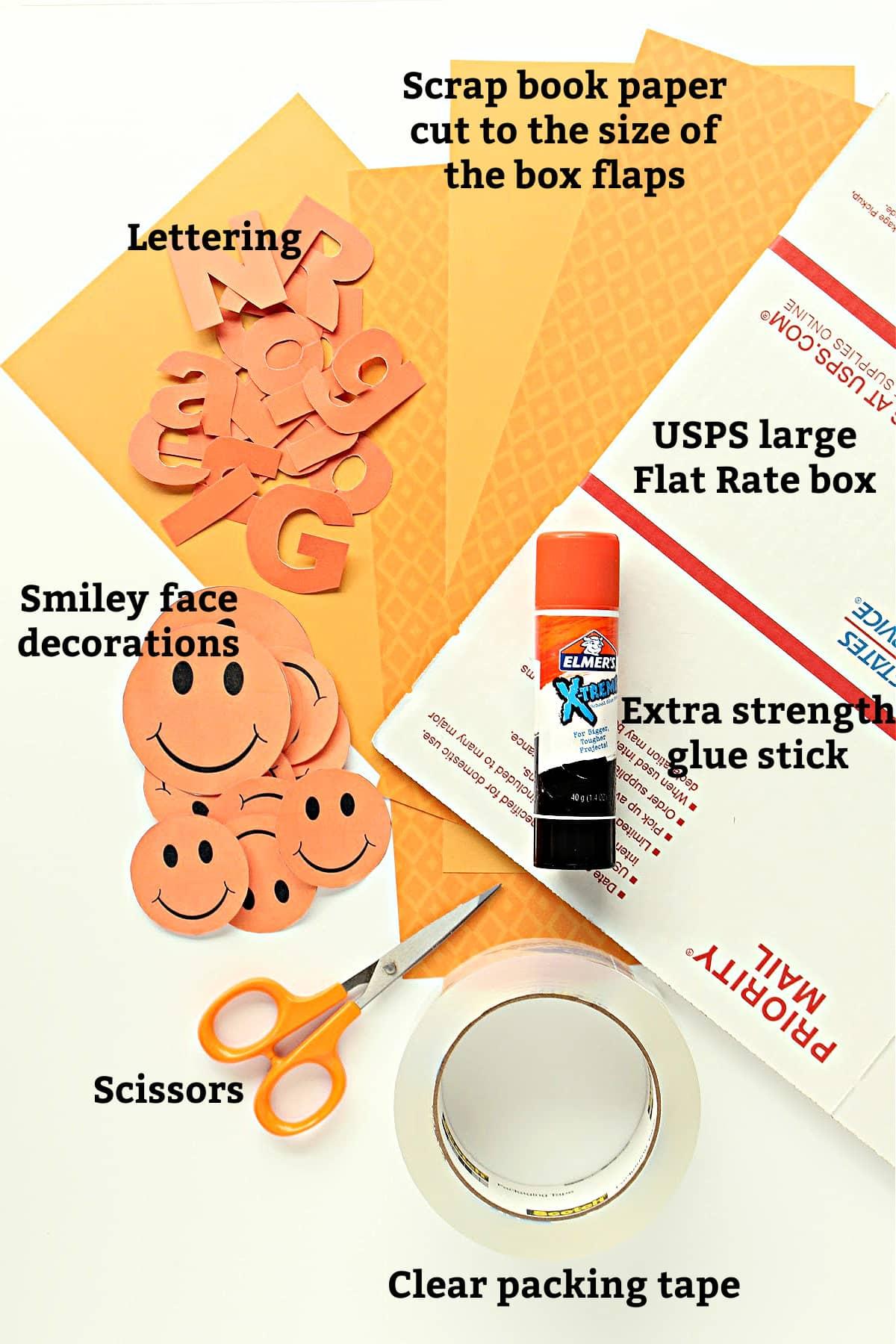 Box decorating supplies; box, glue stick, scissors, packing tape, orange paper, orange lettering, smiley decorations.