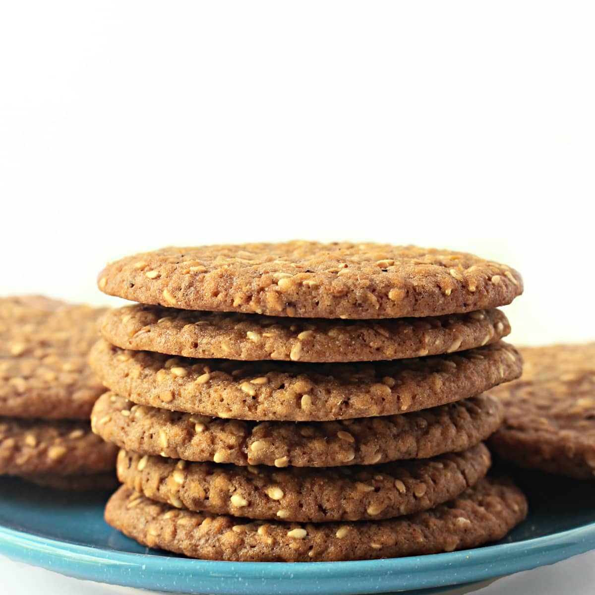 Stack of thin sesame cookies on a blue plate.