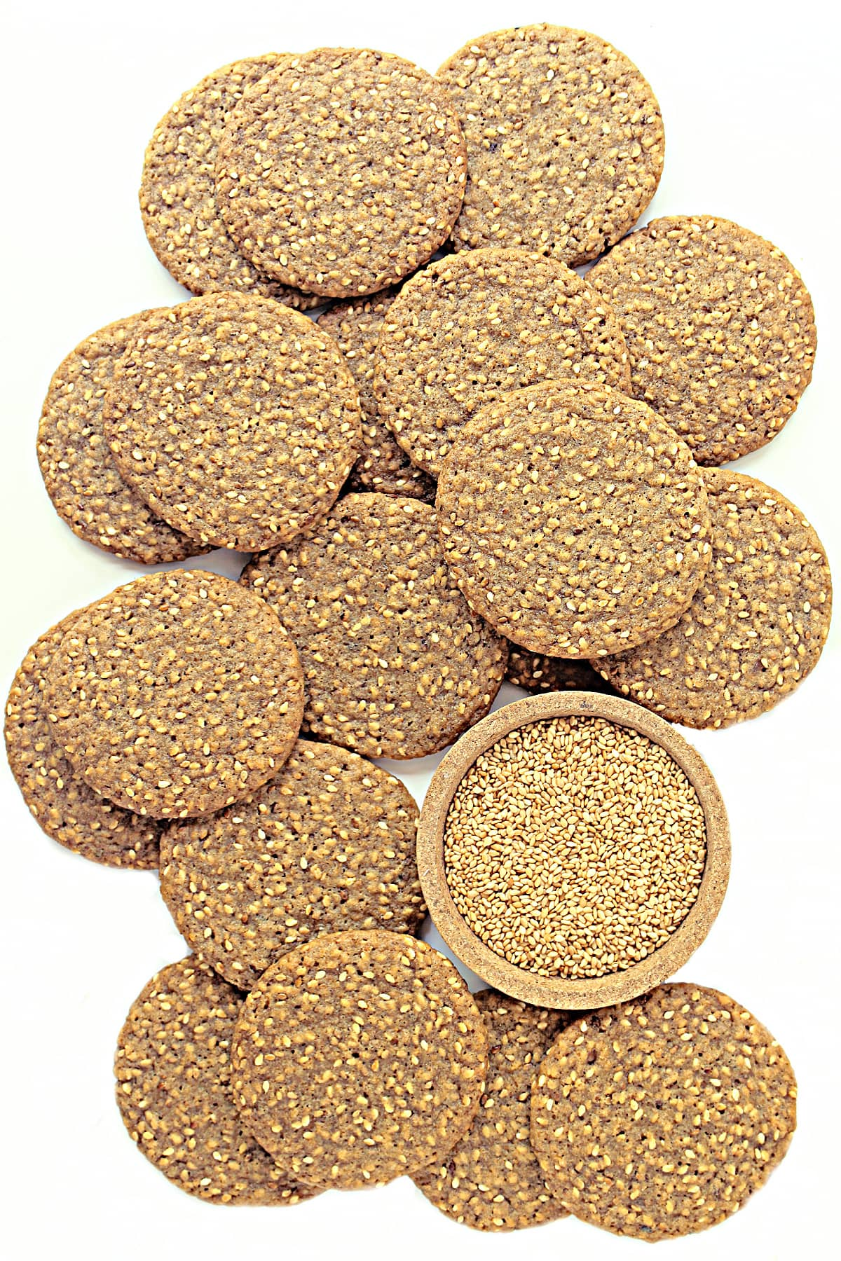 Brown sesame wafer cookies with a bowl of toasted sesame seeds on a white background.