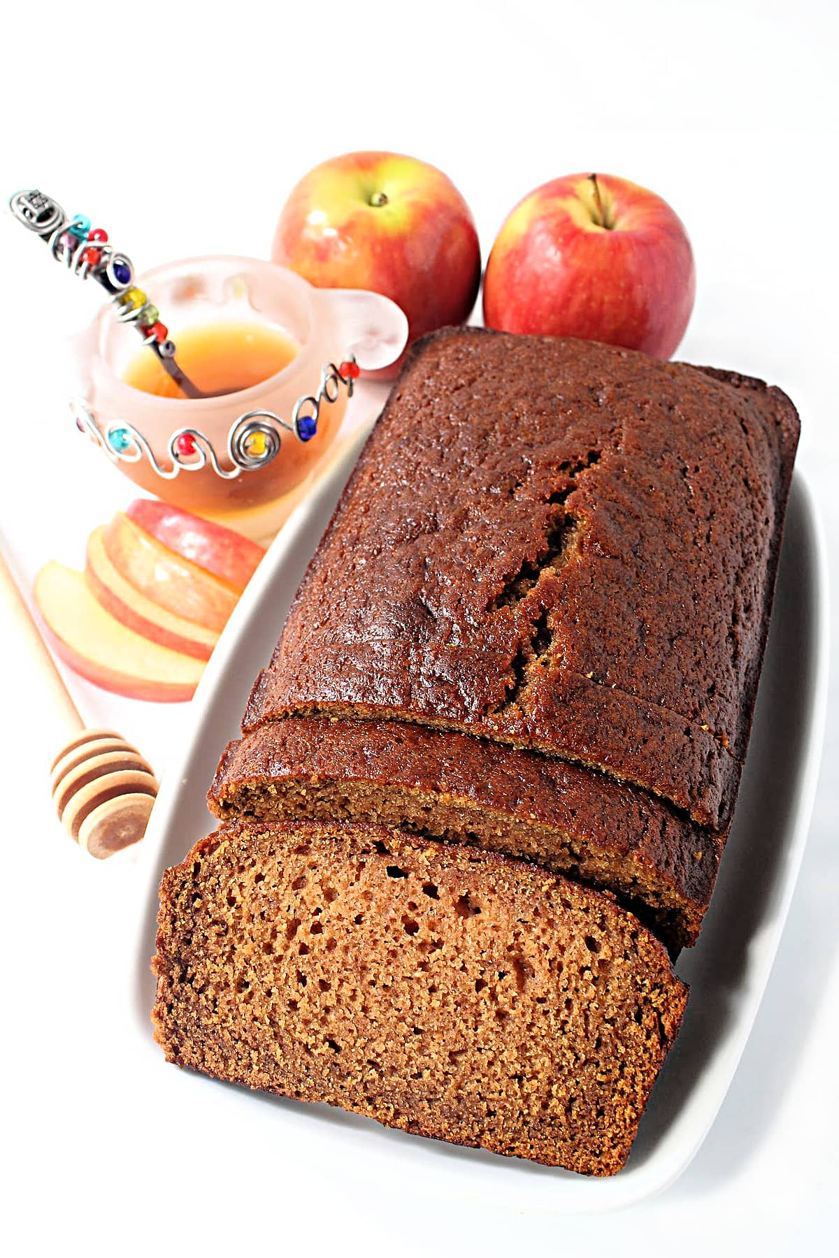 A shiny loaf of sliced Applesauce Honey Cake on a platter with apples and  honey bowl.