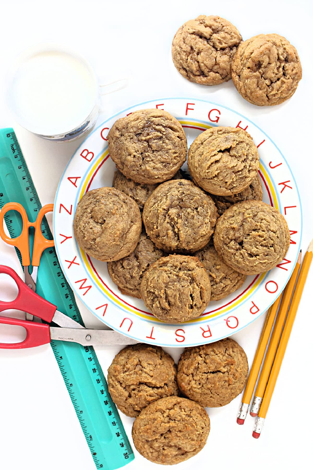 Golden brown peanut butter and jelly cookies on a plate with the alphabet around the rim.